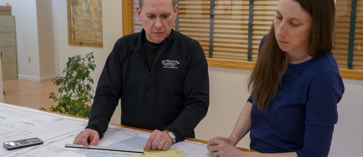 steve salsbury and tara hartson looking over a survey map