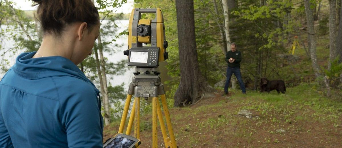 tara hartson using surveying equipment