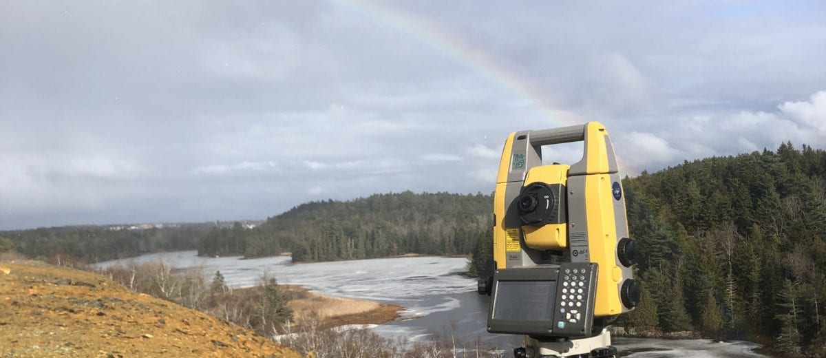 surveying equipment on a hill overlooking a river with a rainbow in the background