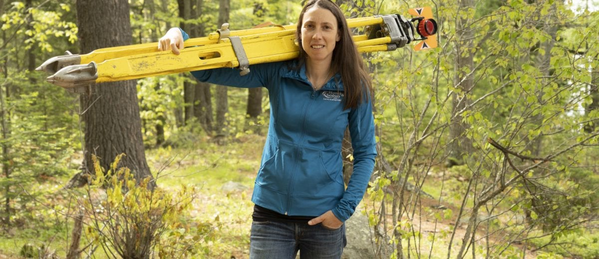 tara hartson posing with surveying equipment