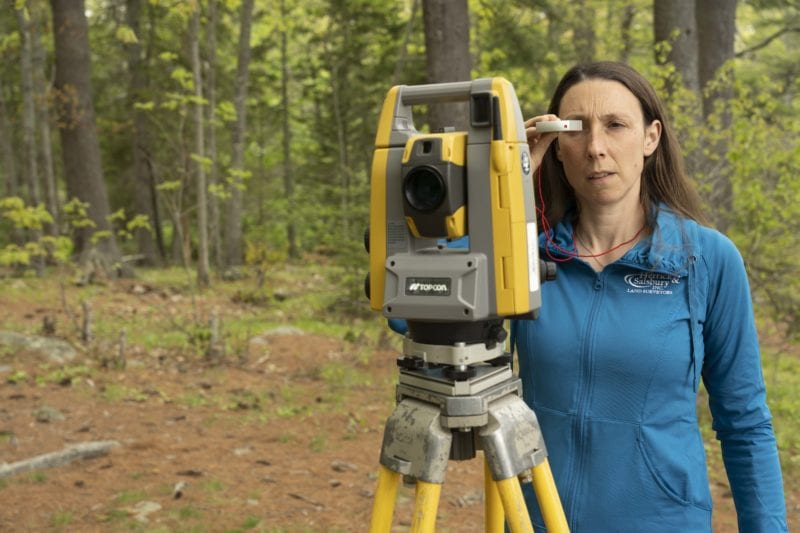 tara hartson using surveying equipment