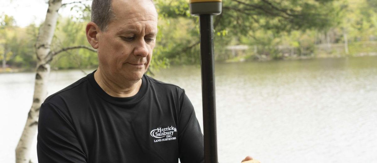steve salsbury using surveying equipment